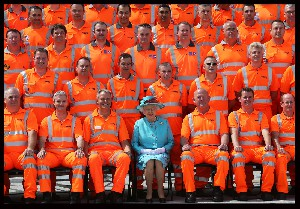 Queen Elizabeth II poses with construction workers for a group photograph after opening Reading Railway Station in Berkshire to mark a £895 million (pounds sterling) re-development of the station